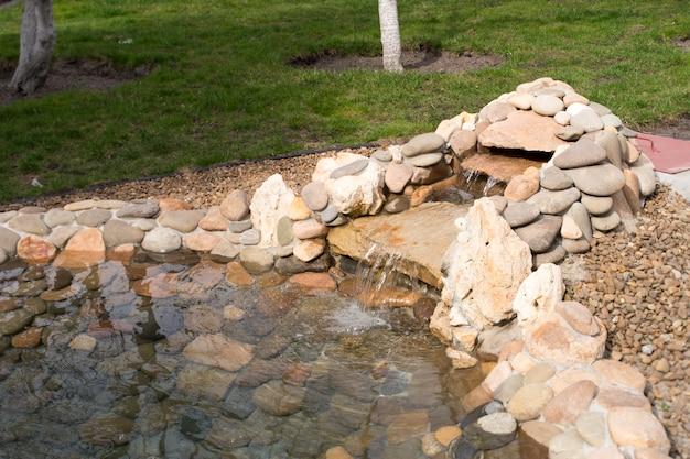 Kunstmatige vijverwaterval in het landschapsontwerp