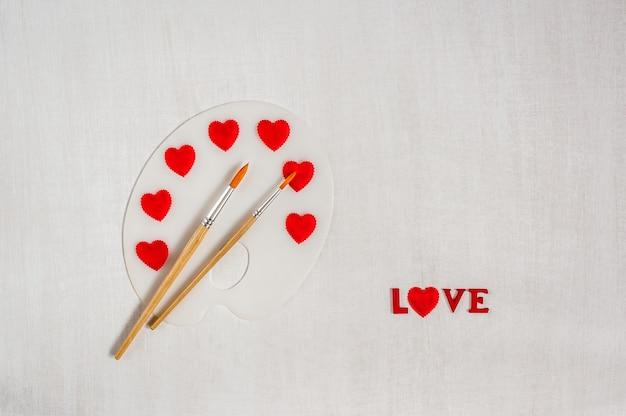 Kunstpalet met rode harten en borstels op witte houten achtergrond.