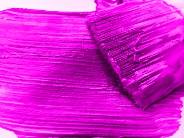 Kunstpenseel gemengde verf op het palet. het palet van de mascotte, textuur gemengde olieverven in roze kleur