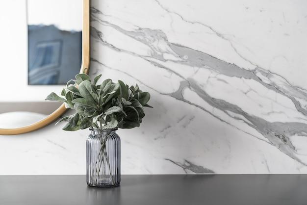 Kunstplant in glazen vaas met gouden roestvrijstalen spiegellijst op grijs gespoten werktafel met marmeren wand
