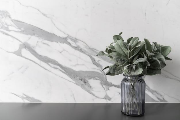 Kunstplant in glazen vaas op grijs gespoten werktafel met marmeren wand