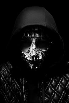 Kunstportret van een man met een kap met grote bergkristallen op zijn gezicht. mysterieuze mystieke verschijning van een man. grote kristallen glinsteren in het donker op het gezicht van de man. wazig onscherp