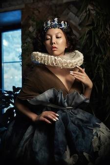 Kunstportret van een meisjesprinses queen in gebladerte en groen, fantastisch romantisch beeld van een aziatische vrouw in een magische jurk. sensuele zachte blik. het meisje in het paleis wacht op de prins