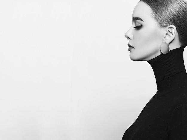 Kunstportret van een mooie, elegante vrouw in een zwarte coltrui en gouden sieraden
