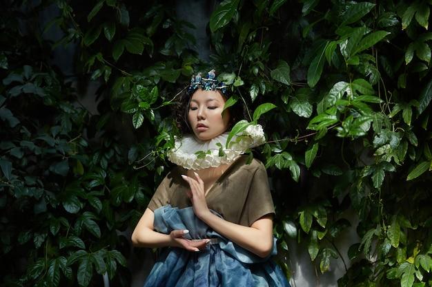 Kunstportret van een prinses queen in gebladerte en groen, fantastisch romantisch beeld van een aziatische vrouw in een magische jurk. sensuele zachte blik. het meisje in het paleis wacht op de prins