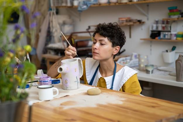 Kunstproces in aardewerkstudio-ambachtsvrouw of professionele keramist die pottenbakkerskruik verfraait te koop