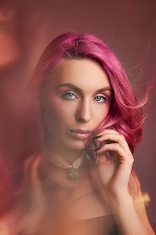 Kunstschoonheidsportret van een vrouw met roze haar, creatieve kleuring. felgekleurde highlights en schaduwen op het gezicht, een meisje met sieraden. geverfd haar in de wind