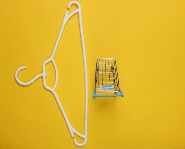 Kunststof hanger en winkelwagentje op geel papier