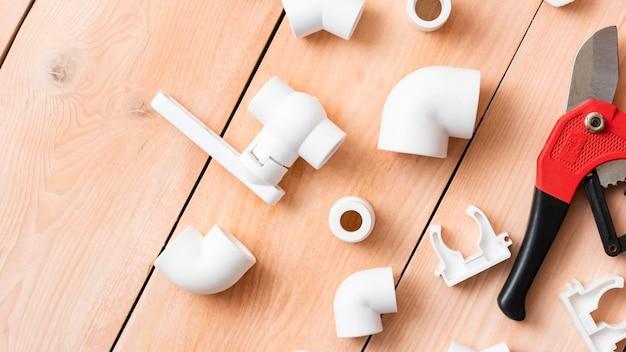 Kunststof onderdelen op een houten tafel voor het watervoorzieningssysteem. bovenaanzicht