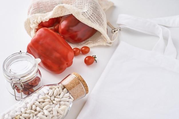 Kunststofvrije herbruikbare producten, geen afval. verse groenten, bonen in een glazen fles en textiel boodschappentas op wit