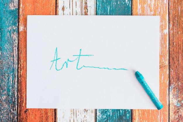 Kunsttekst op wit papier over oude houten tafel met blauw kleurpotlood