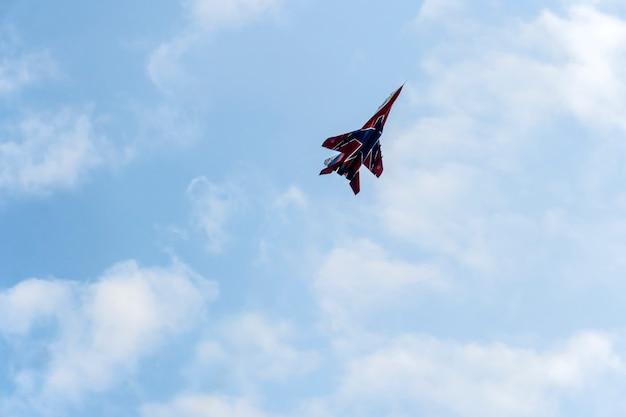 Kunstvliegen van russische ridders en gierzwaluwen. russische militaire vliegtuigen tonen kunstvluchten in de blauwe lucht tegen de achtergrond van wolken.