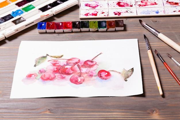 Kunstwerk, aquarel kersen met tekengereedschap op een houten tafel