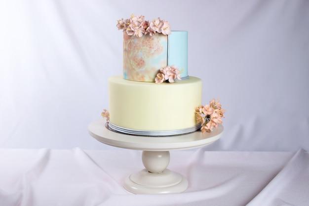 Kunstwerk. bruidstaart versierd in pastel stijl met roze bloemen