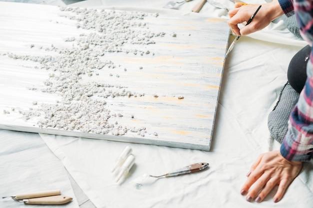 Kunstwerk in bewerking. kunstenaar talent en stijl. reliëfpatroon canvas op de vloer. vrouw met borstel.