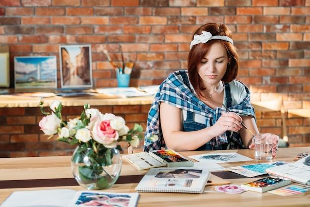 Kunstwerken maken. kunstenaar doet aquarel. schetsboek en paletbenodigdheden in de buurt.