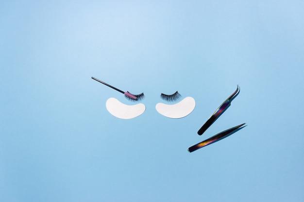Kunstwimpers, patches en pincetten op een blauwe achtergrond, bovenaanzicht