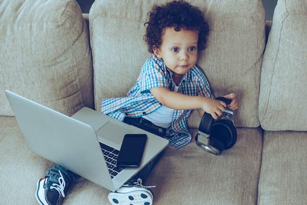 Kunt u alstublieft mijn digitale tablet meenemen? hoge hoekmening van kleine afrikaanse babyjongen die koptelefoon vasthoudt en wegkijkt terwijl hij thuis op de bank zit met laptop en smartphone op zijn knieën