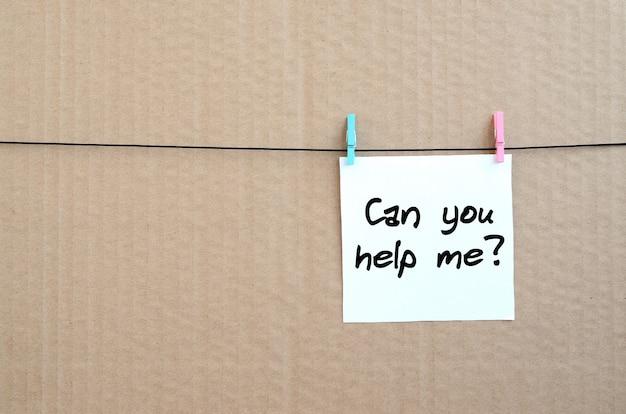 Kunt u mij helpen? opmerking staat op een witte sticker die met een wasknijper aan een touw op een achtergrond van bruin karton hangt