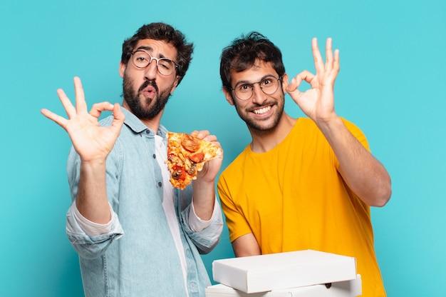 Kuople van twee spaanse vrienden met een gelukkige uitdrukking en met afhaalpizza's