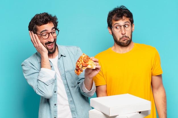 Kuople van twee spaanse vrienden verraste uitdrukking en hield afhaalpizza's vast