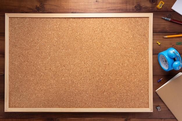 Kurkbord en kantoorbenodigdheden op houten tafel achtergrondtextuur