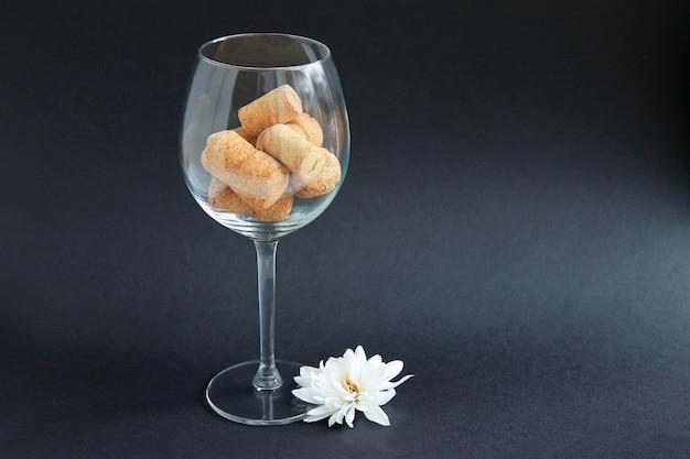 Kurken van wijnflessen zijn in het wijnglas op een donkere achtergrond