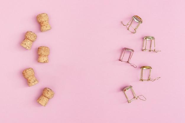 Kurkt en muselets van champagne mousserende wijn op roze gekleurde achtergrond met kopie ruimte. kerstmis en gelukkig nieuwjaar concept. plat liggen.