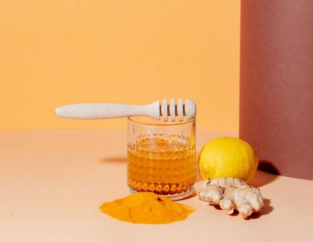 Kurkuma, honing, citroen en gember naast een glas