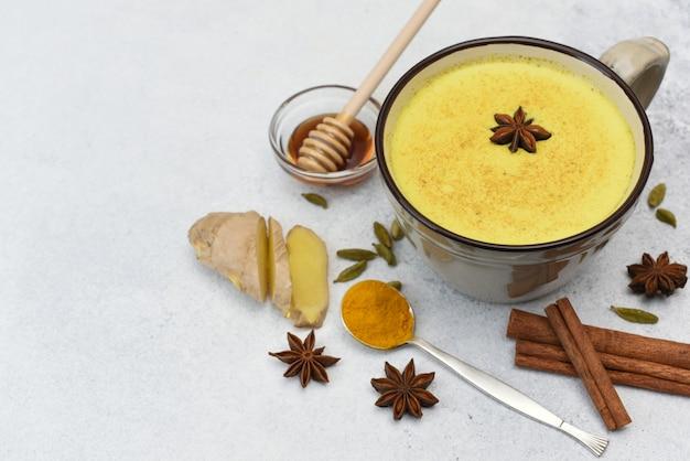 Kurkuma latte bovenaanzicht. gouden melk in kop met rond steranijs en kruiden. warme gezonde ayurvedische drank. kurkuma, kaneel, gember, honing, steranijs, kardemom.