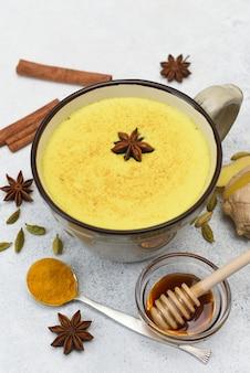 Kurkuma latte bovenaanzicht. gouden melk in kop met rond steranijs en kruiden.