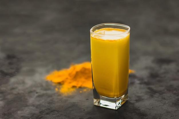 Kurkuma latte, een gouden melkachtig warme gezonde drank op een donkere achtergrond in een glazen beker