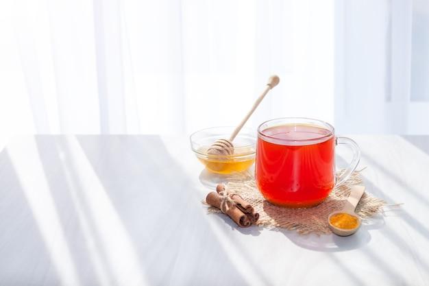Kurkuma-thee met honing, kaneel in de ochtend. detox, gezond drankje concept.