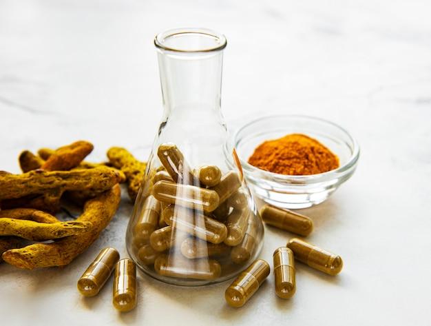 Kurkuma wortels, poeder en reageerbuis met pillen