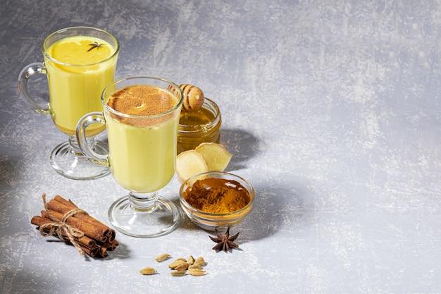 Kurkumamelk voor immuniteit. twee glazen glühwein met gouden melk met ingrediënten op lichtgrijze achtergrond.