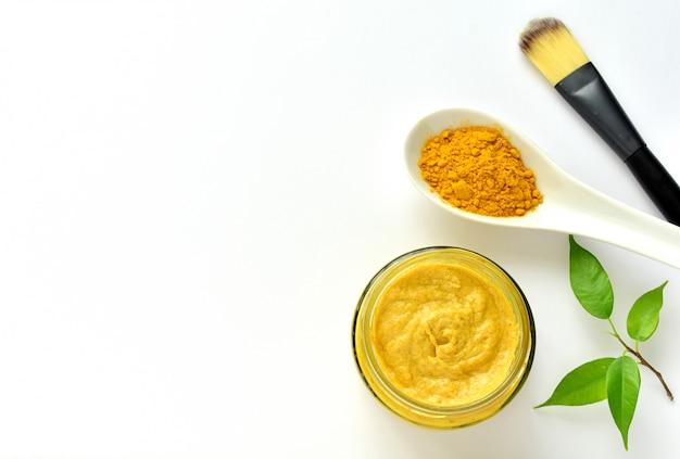 Kurkumapoeder en zelfgemaakt gezichtsmasker voor acnehuid in kleine glazen pot.