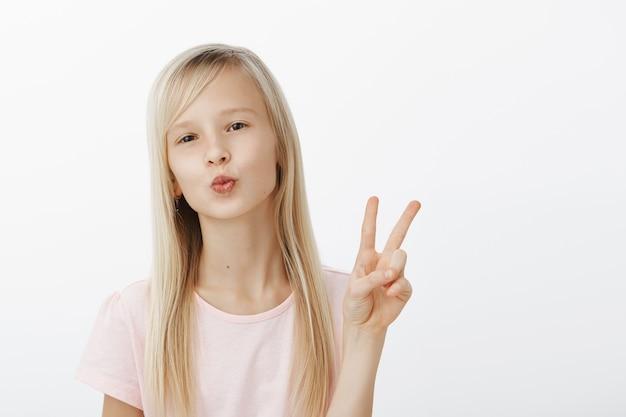 Kus aan mijn volgers, blijf op de hoogte. portret van modieus zelfverzekerd jong meisje met natuurlijk blond haar, lippen vouwen, kus blazen, vrede of overwinningsteken tonen, in goed humeur over grijze muur