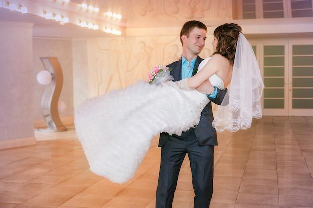 Kus en dans jonge bruid en bruidegom in feestzaal