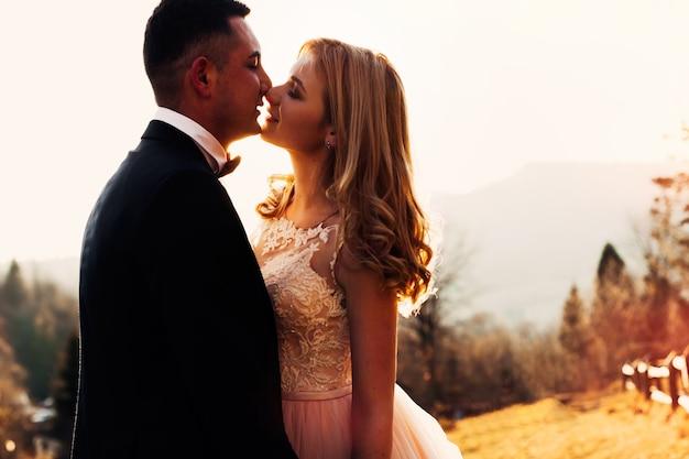 Kus van de pasgetrouwden op bergen bruid met mooi kapsel en jurk met kant