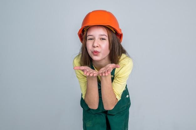 Kusjes sturen. elektricien blaas kusjes. meisje in helm speelt bouwer. bouwen en verbouwen. kind bouwen constructie. ingenieur tiener is bouwvakker. internationale dag van de arbeid.