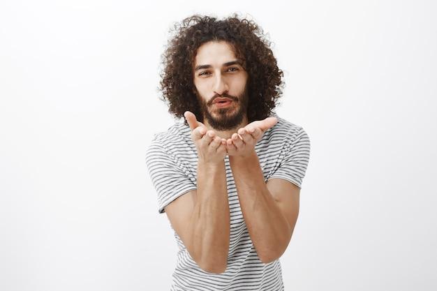 Kusjes sturen naar mijn liefde. portret van charmant knap mannelijk model met krullend haar en baard