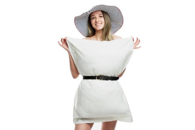 Kussen challenge. glimlachend meisje in een hoed en een witte kussensloop. flash mob tijdens de periode van de pandemie van het coronavirus. geïsoleerd op een witte muur.