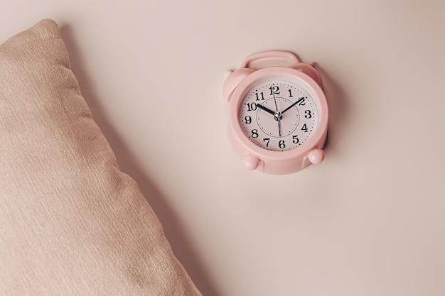 Kussen en wekker op een beige achtergrond. gezond rustgevend slaapconcept.