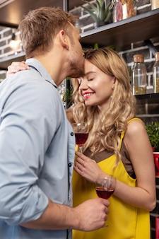 Kussen en wijn. liefdevolle man met baard die zijn mooie stralende vrouw kust terwijl hij wijn drinkt