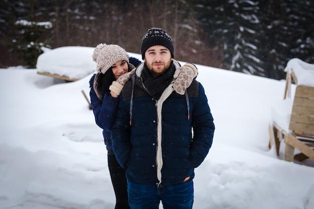 Kussen liefdevol paar in winterkleren, tijdens een sneeuwval op een dennenbos