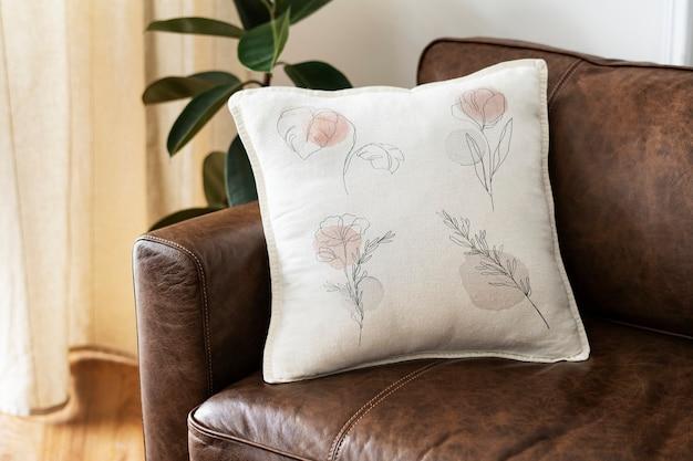Kussen met minimale bloemenlijnkunst op een leren bank