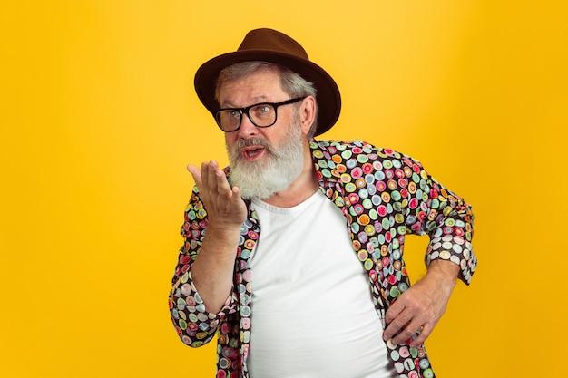 Kussen verzenden portret van senior hipster man in brillen geïsoleerd op gele studio achtergrond