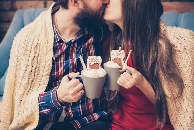 Kussend paar: man en vrouw met warme koffiemokken en marshmallow. bijgesneden afbeelding