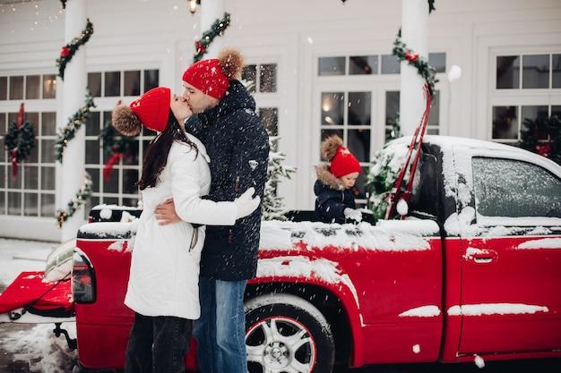 Kussende ouders in rode hoeden onder sneeuwval buitenshuis. mooie jongen in rode hoed spelen in rode pick-up op de achtergrond.