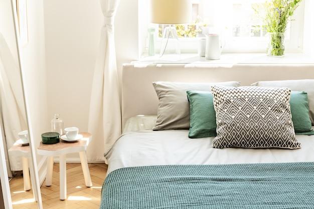 Kussens en groene lakens op bed in slaapkamer interieur met witte tafel naast spiegel. echte foto
